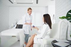 Beautician рекомендуя эффективный продукт заботы кожи к молодой женщине стоковые изображения rf