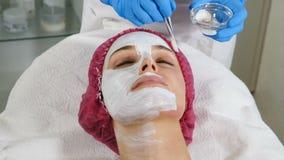 Красивая женщина с лицевой маской на салоне красоты Приложение лицевой маски на стороне женщины на салоне красоты Терапия спа для видеоматериал