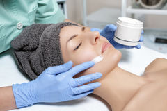 Beautician applies face cream on young woman in Spa salon. cosme Stock Image