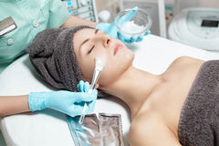 Beautician applies face mask with brush to beautiful young woman in Spa salon. cosmetic procedure skin care. Royalty Free Stock Photo