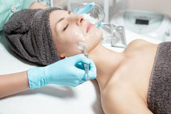 Beautician applies face mask with brush to beautiful young woman in Spa salon. cosmetic procedure skin care. Stock Photography