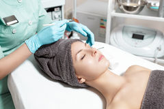 Beautician applies face mask with brush to beautiful young woman in Spa salon. cosmetic procedure skin care. Stock Images