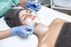 Beautician applies face mask with brush to young woman in Spa sa Royalty Free Stock Photo