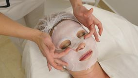 Beautician applies facial mask to the girl`s skin.  stock video