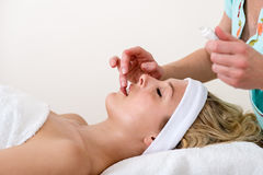 Beautician applying balm on the lips of a woman. Stock Photo