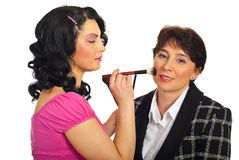 Beautician applying blush on mature face Royalty Free Stock Photography