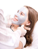 Beautician applying a clay face mask Stock Photography