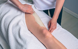 Beautician applying clay treatment in woman legs on spa Stock Images