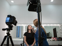 Beautician applying cosmetics to blogger. Beautician putting makeup on beauty blogger at the camera. Backstage shot of artist workshop royalty free stock photography