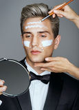 Beautician applying cream by brush on man& x27;s face. Stock Photography
