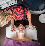 Beautician Applying Facial Mask To Woman In Salon Stock Images