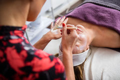 Beautician Applying Facial Mask On Woman's Face Royalty Free Stock Image