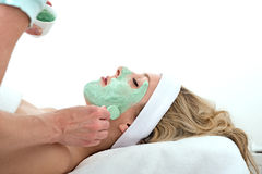 Beautician applying green facial mask on a woman. Stock Photos