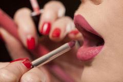 Beautician applying lipstick to a model Royalty Free Stock Photography