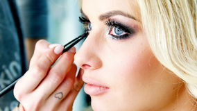 Beautician applying makeup to a beautiful blond model stock footage