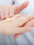 Beautician applying moisturizing cream on client hands. Beauty salon Stock Photo