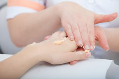 Beautician applying moisturizing cream on client hands. Beauty salon Stock Image