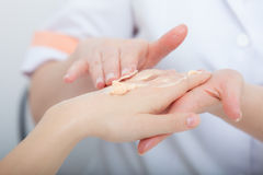 Beautician applying moisturizing cream on client hands. Beauty salon Royalty Free Stock Images