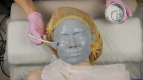 Beautician applying mud mask for woman face in the spa salon. facial rejuvenation procedure, spa treatments.  stock video