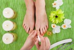 Beautician applying nail varnish to woman Stock Photo