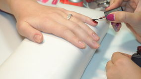 Beautician applying Polish nails to women nails stock video footage