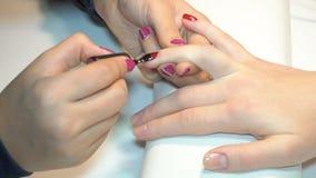Beautician applying Polish nails to women nails stock video