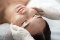 Beautician applying scrub on female face. Close up of young woman getting facial skin treatment at spa. Cosmetician hands applying peeling mask on her face Stock Photos