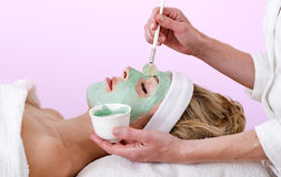 Beautician applying a thalasso face mask. Royalty Free Stock Photo