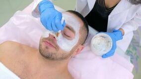 Beautician is applying white mask on man client face in beauty clinic, closeup.