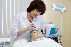 Beautician in beauty salon makes eyebrow tattooing. For woman Royalty Free Stock Photography