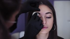 A beautician in black gloves using a white clean cotton disk ank little brows brush to remove the paint from the brows A. Woman sits in the chair during a visit stock video