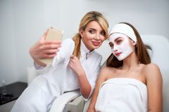 Beautician blogger making selfie with client after applying facial mask for healthy skin. Attractive women making photos stock image