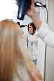 Beautician Blow Drying Hair Of Female Customer Stock Photography