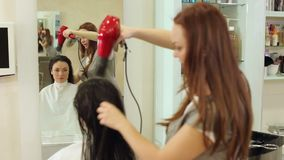 Beautician blow drying woman`s hair after giving a new haircut at parlor. Professional hairdresser drying hair of a young girl stock footage