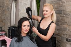 Beautician blow drying womans hair after giving new haircut at parlor. Royalty Free Stock Photos