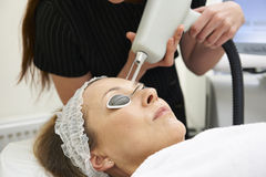 Beautician Carrying Out Fractional Laser Treatment. Female Beautician Carrying Out Fractional Laser Treatment Stock Photo
