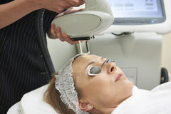 Beautician Carrying Out Intense Pulse Light Treatment. Female Beautician Carrying Out Intense Pulse Light Treatment Stock Image