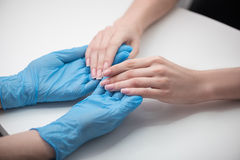 Beautician is checking cuticles of girl. Nails caring. Young women are sitting at table. Close up top view of fingernails of client, which is holding manicurist Royalty Free Stock Photography