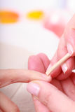 Beautician cleaning cuticles hands with cosmetic stick. Beauty spa salon Stock Images