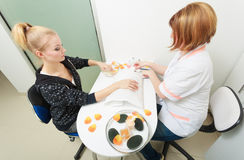 Beautician cleaning cuticles hands female client. Beauty salon. Royalty Free Stock Photos