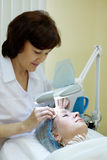 Beautician cleans facial skin of woman Stock Photo