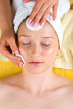 Beautician cleansing young woman face Stock Images