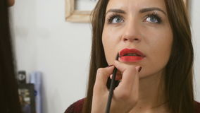 Beautician colors woman`s lips with red lipstick stock footage