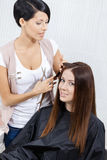 Beautician cuts hair of woman in hair stylist's Stock Photos