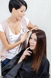 Beautician cuts hair of woman in hairdress salon Royalty Free Stock Photography