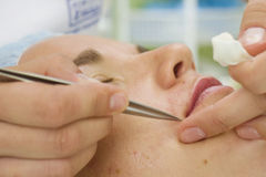 Beautician, der eine Frau mit Pinzette depilating ist Lizenzfreies Stockbild