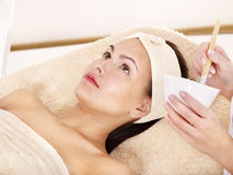 Beautician, der Gesichtsschablone durch Frau anwendet. Stockbild
