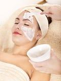 Beautician, der Gesichtsschablone durch Frau anwendet. Stockfoto