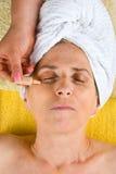 Beautician, der Serum am älteren Gesicht anwendet Stockbild