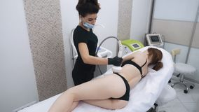 Beautician do lifting therapy on woman body uses contouring device, slow motion. Anti-cellulite procedure stock video footage